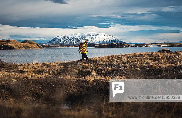 Frau geht durch ein Feld neben einem See mit Bergen in der Ferne