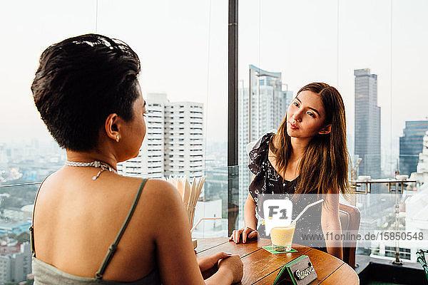 Frauen sitzen an einer Rooftop Bar