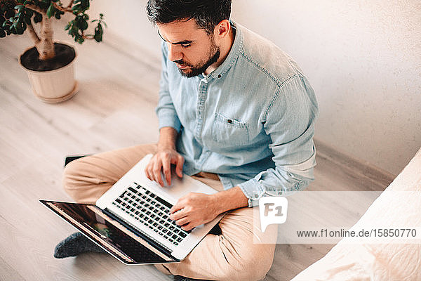Serious man using laptop computer while sitting on floor at home