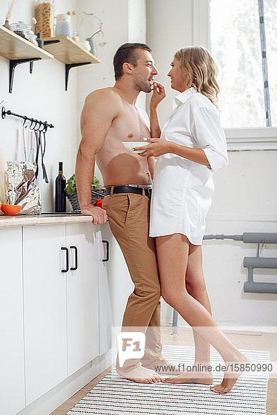 Eine sexy Frau in Unterwäsche und ein Mann ohne Hemd verbringen Zeit miteinander.