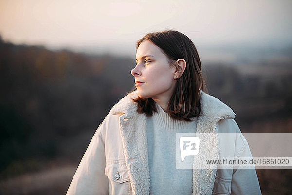 Porträt einer schönen jungen Frau in warmer Kleidung bei Sonnenuntergang