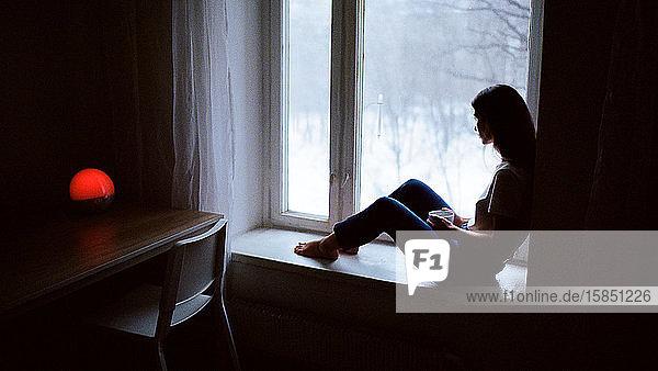 Porträt einer Frau  die auf einem Fensterbrett sitzt