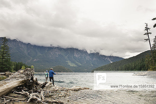 Man and Child Fishing at a Lake Surrounded by Mountains in Washington