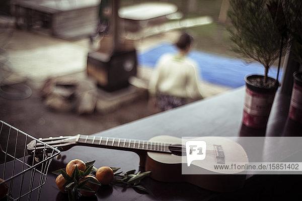 Akustische Gitarre liegt auf dem Tisch mit frisch gepflücktem Obst über dem Kamin