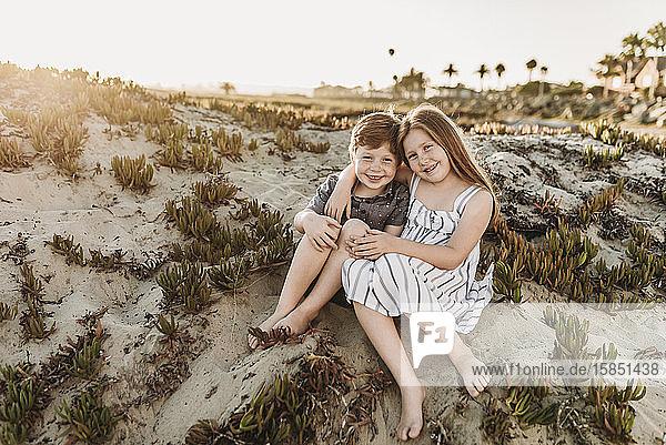 Frontansicht der jungen rothaarigen sommersprossigen Geschwister am Strand sitzend