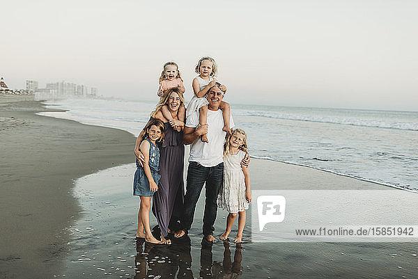 Traditionelles Porträt einer Familie mit vier Kindern  die in der Strandsonne lächeln