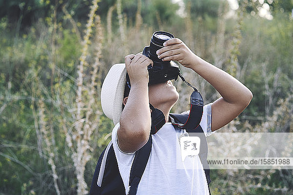 Kid photographer with white hat taking photos with his camera