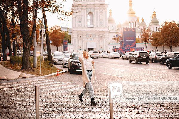 Junge stilvolle Frau überquert Straße in der Stadt