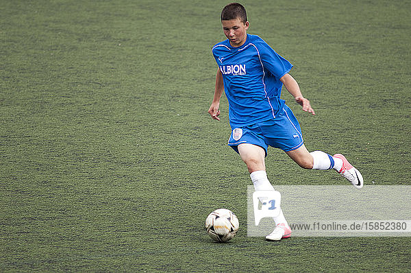 Teen soccer player dribbling the ball during a game