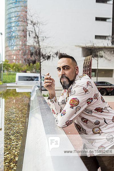 Hübscher stilvoller junger Mann raucht in der Pause draußen