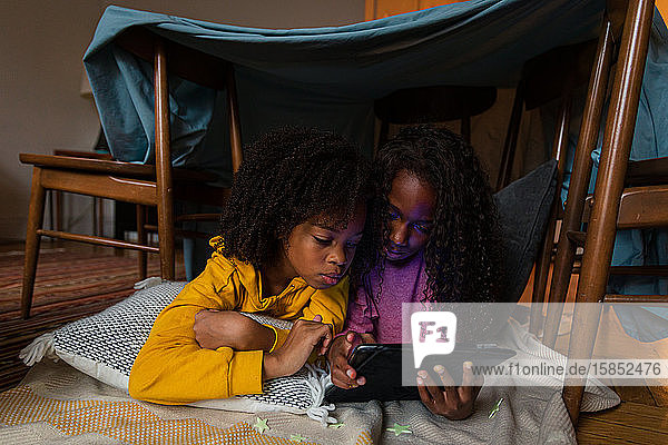 Sisters using digital tablet while lying at home