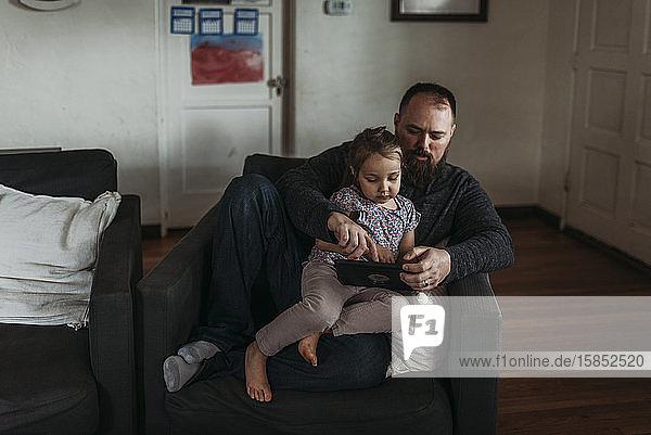 Vater und kleine Tochter spielen während der Isolation auf dem Tablett