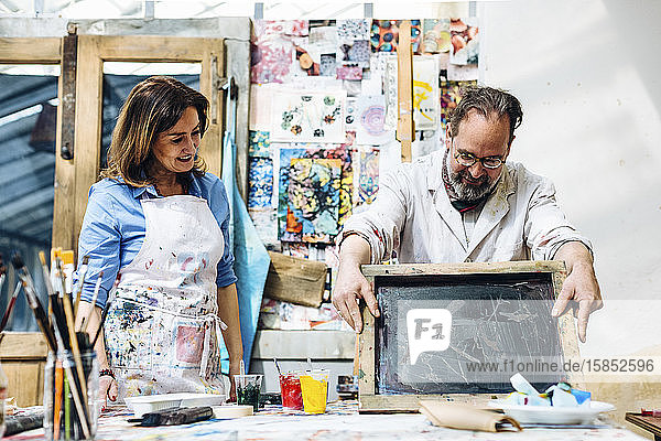 Inspired mature artisans working in screen printing studio