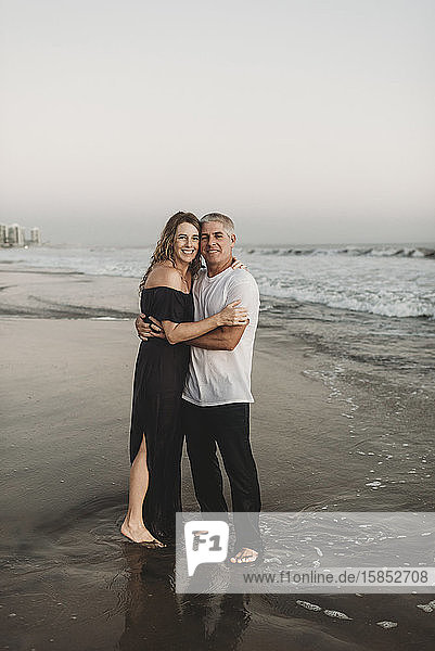 Tranditional portrait of married couple standing in ocean at sunset