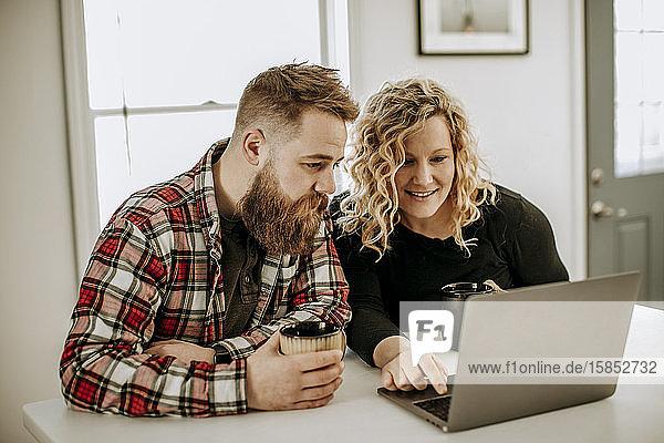 junges heterosexuelles Paar sitzt am Tisch und schaut auf Laptop-Computer