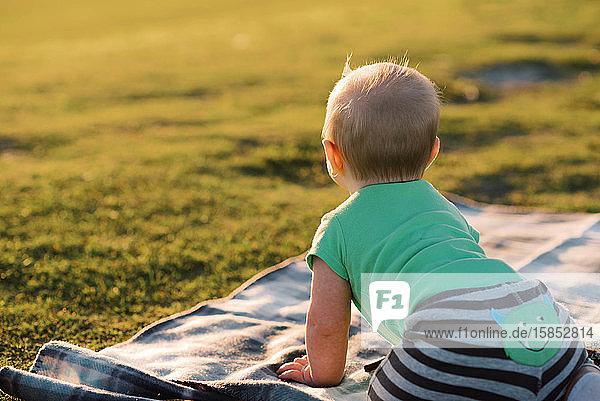 Kleiner Junge im Park bei Sonnenuntergang.