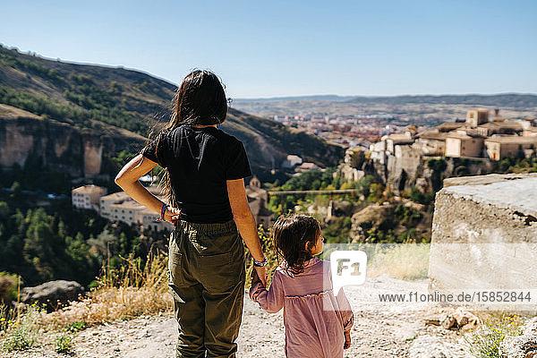 Junge Mutter mit ihrer kleinen Tochter  die Händchen hält und auf das Sein schaut