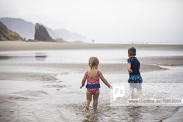 Brother and sister run through shallow water at the beach.