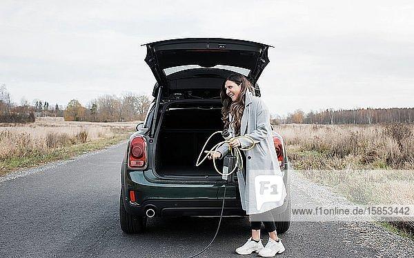 Frau  die ein Ladegerät für ein Elektroauto in den Kofferraum ihres Autos legt
