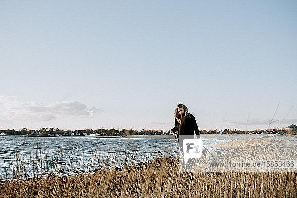 Frau  die im Winter mit dem Hund am Strand spazieren geht