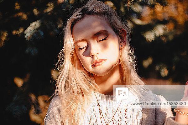 Porträt einer jungen Frau mit geschlossenem Editor vor dem Sonnenlicht stehend