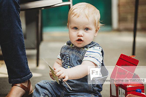 Süßes sitzendes Baby schaut auf Kamera und hält Puzzle