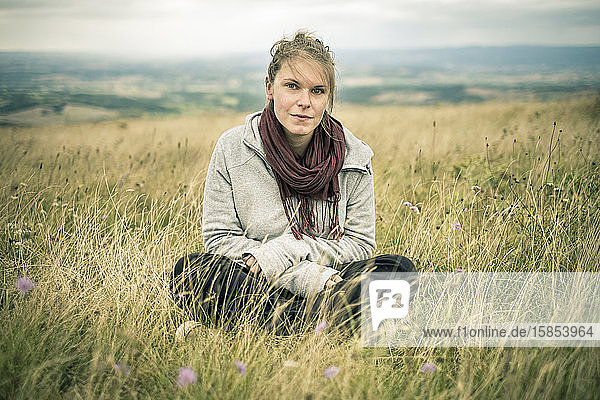 Young woman sitting in grassy meadow looking at camera