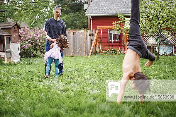 Ein Vater spielt mit kleinem Mädchen im Hof  während der Junge Purzelbäume schlägt