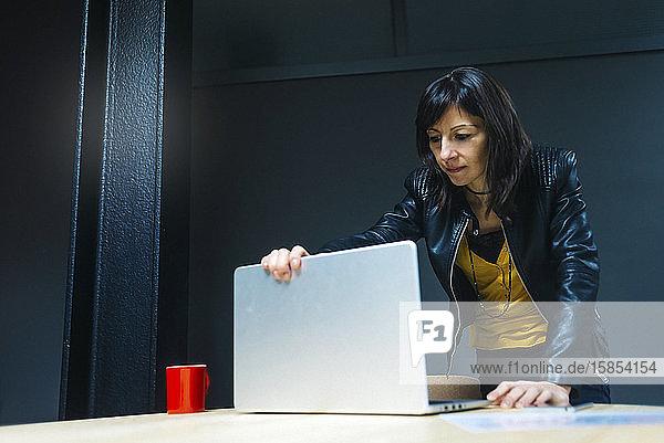 Weibliche Geschäftsfrau betrachtet Laptop im Büro