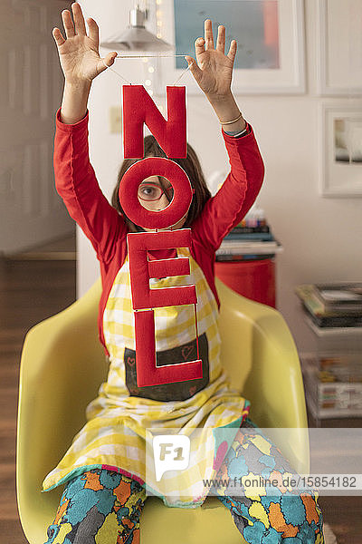 Child holding Noel Banner at home