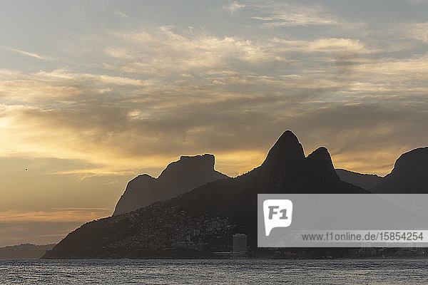 Beautiful sunset view to ocean with mountains and clouds from Ipanema