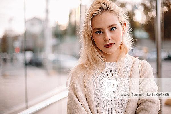 Porträt einer jungen selbstbewussten Frau  die an einer Bushaltestelle in der Stadt steht