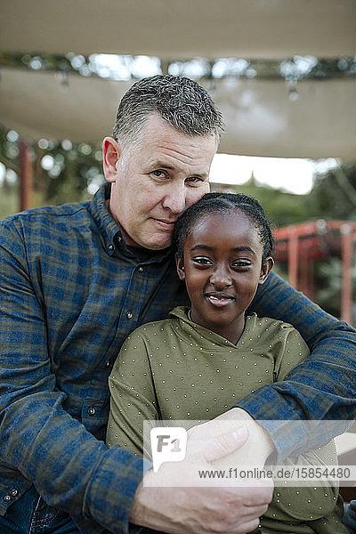 Papa Mitte der 40er Jahre umarmt lächelnde junge schwarze Tochter