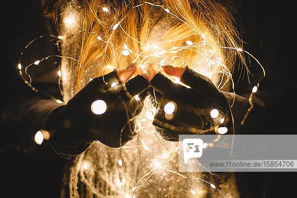 Nahaufnahme einer Frau  die im Dunkeln Weihnachtsbeleuchtung im Freien hält