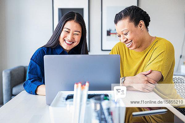 Lächelnde Mitarbeiterinnen diskutieren über Laptop am Tisch im Büro