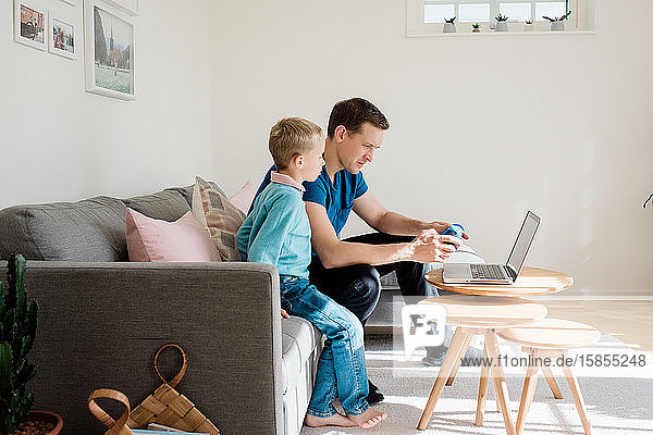 father and son looking at a laptop together at home