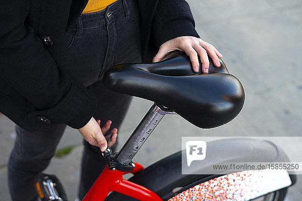 Frau  die den Sattel des Fahrrads einstellt.