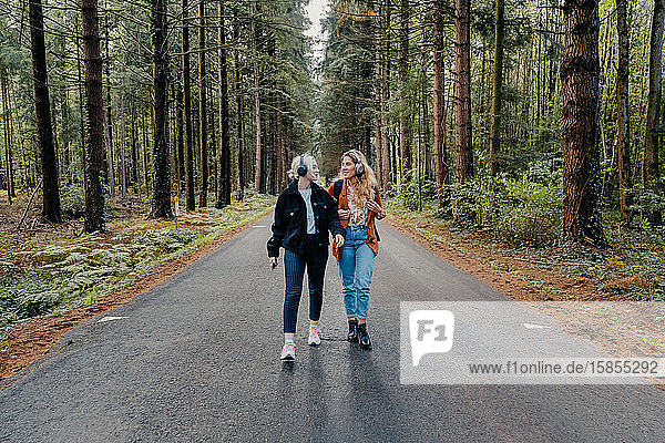 Zwei Frauen gehen auf einer Straße im Wald spazieren  während sie Musik hören