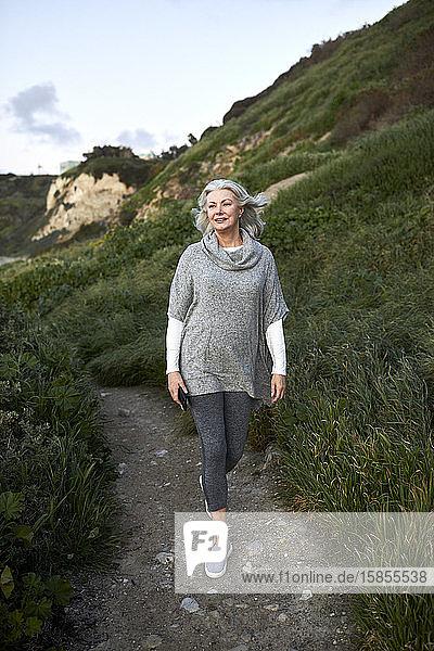 Ältere Frau in voller Länge geht bei Sonnenuntergang am Manhattan Beach auf einem Fußweg