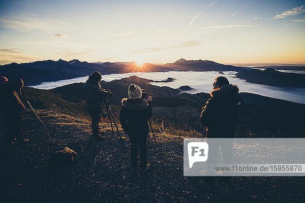 Fotografen bei Sonnenaufgang auf dem Gipfel des Berges