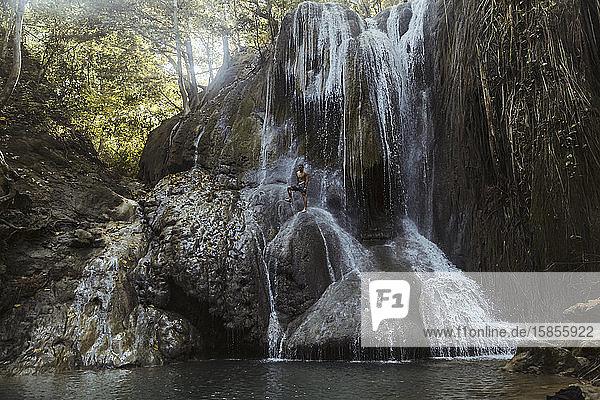 Mann klettert auf Wasserfall