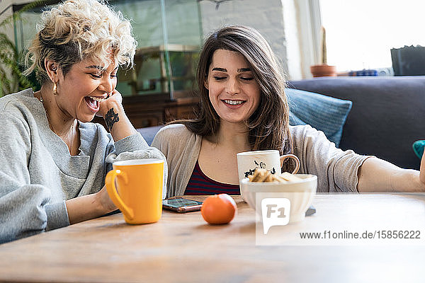Glückliche weibliche Mitbewohnerinnen benutzen ein Smartphone,  während sie Kaffee bei Tisch trinken