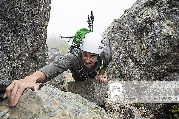 Hochwinkelansicht eines Bergsteigers  der nach einem Handgriff greift.