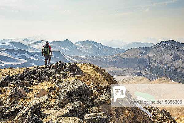 Backpacker hiking on mountain summit.