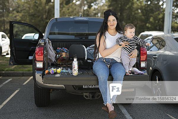 Eine junge Frau und ihr Baby sitzen auf der Heckklappe eines Lastwagens an einer Raststätte.