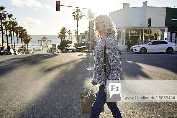 Seitenansicht einer älteren Frau mit Einkaufstasche  die bei Sonnenuntergang in der Stadt auf der Straße geht