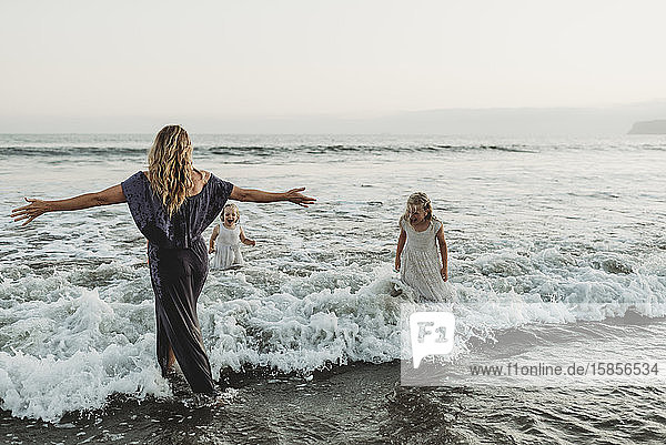Mom and two young girls splashing in ocean at sunset