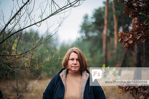 Nahaufnahme-Porträt einer im Wald stehenden Frau