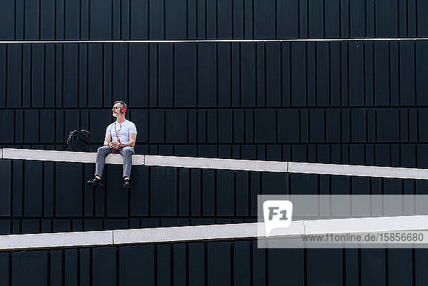 Mature man sitting on a wall listening to music with headphones