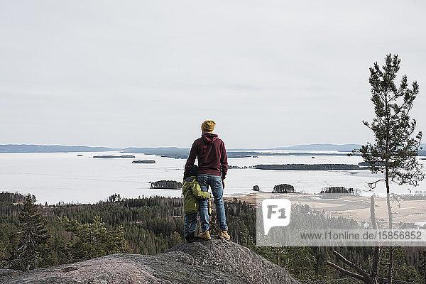 Vater und Sohn stehen gemeinsam auf einem Hügel und genießen die Aussicht